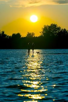 Duas silhuetas de uma criança e um cachorro no reflexo da água em um fundo do sol. lazer infantil e férias.