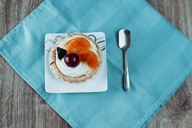 Duas sobremesas, uma de chocolate com cerejas, a outra de creme branco com ameixas e tangerinas