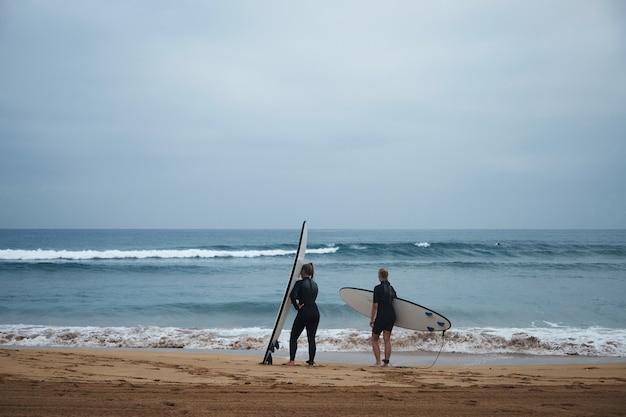 Duas surfistas irreconhecíveis com seus longboards ficam na costa do oceano e observam as ondas no início da manhã, vestindo roupas de neoprene completas e prontas para surfar
