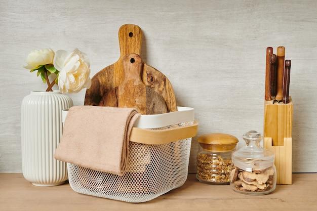 Duas tábuas de cortar de madeira e toalhas em uma cesta ao lado de um vaso de flores