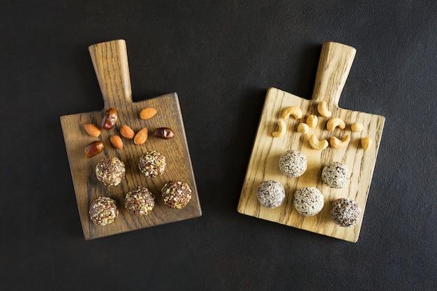 Duas tábuas de madeira com bolas de energia doce com nozes e frutas secas planas sobre fundo escuro