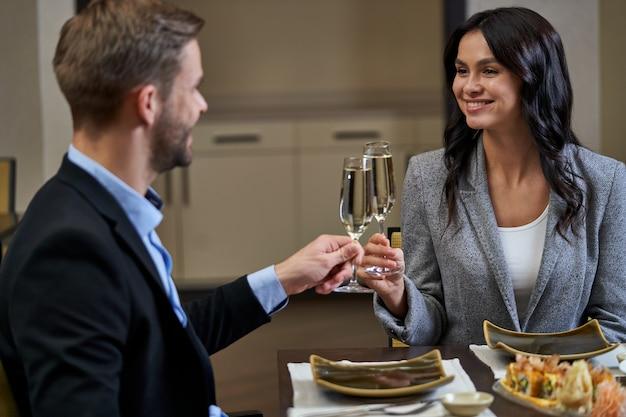 Duas taças cheias de champanhe tilintando na mesa de jantar nas mãos de um homem e uma mulher de negócios