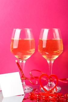 Duas taças com champanhe amarradas com fitas vermelhas em uma superfície rosa ao lado de um cartão postal