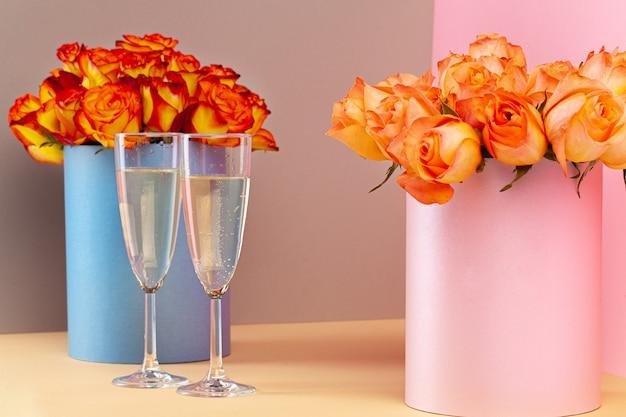 Duas taças com champanhe e buquê de rosas