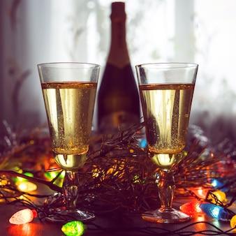 Duas taças com champanhe e garrafa sobre uma mesa de madeira decorada com acessórios de natal para celebrar o ano novo e o natal. noite romantica. o brilho das guirlandas. dia dos namorados