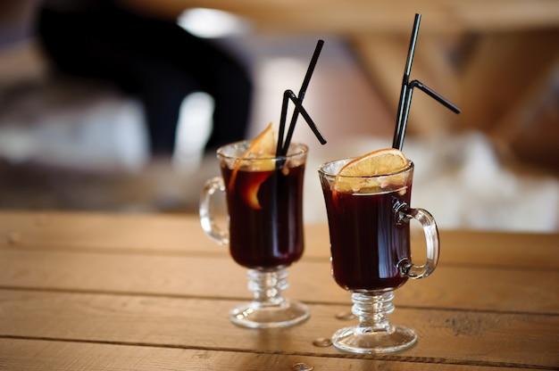 Duas taças com saboroso vinho quente quente com especiarias em uma mesa de madeira no café