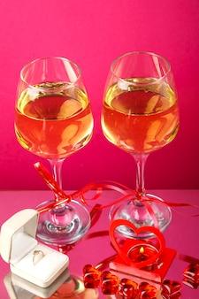 Duas taças de champanhe amarradas com fitas em um fundo rosa ao lado de um anel em uma caixa e uma vela em um castiçal