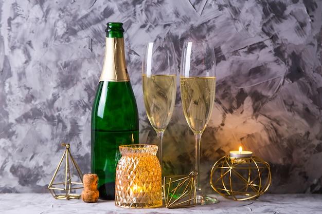 Duas taças de champanhe ao lado de uma garrafa e decoração de natal de cor dourada