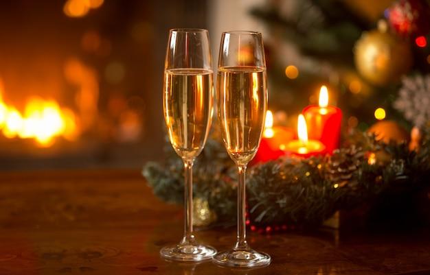 Duas taças de champanhe cheias na frente da guirlanda de natal com velas acesas