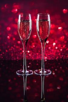 Duas taças de champanhe com bokeh de forma de coração vermelho no fundo. jantar romântico. feliz dia dos namorados conceito.