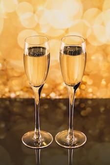 Duas taças de champanhe com bokeh de luz dourada no fundo. jantar romântico. conceito de férias de inverno.