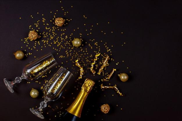 Duas taças de champanhe com confetes em fundo preto.