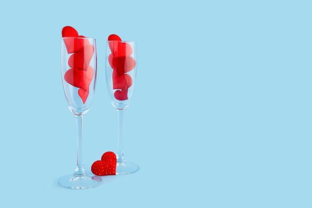 Duas taças de champanhe com corações vermelhos em azul. feliz jantar de dia dos namorados.
