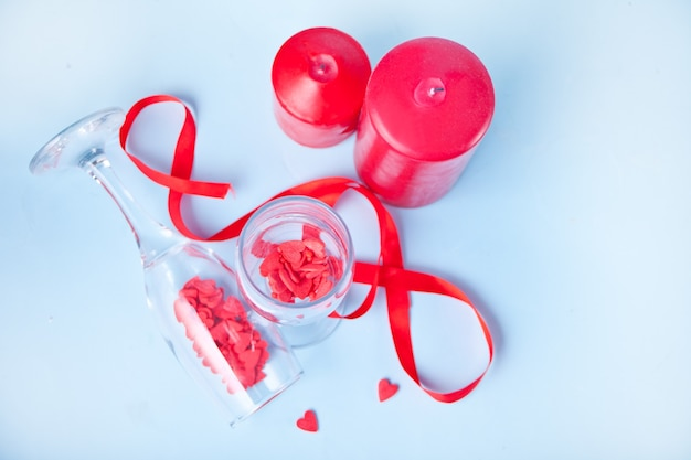 Duas taças de champanhe com doces em forma de coração vermelho e velas vermelhas no fundo. conceito de dia dos namorados.