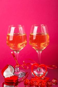 Duas taças de champanhe com fitas vermelhas ao lado de um castiçal de coração com uma vela acesa e um anel de caixa