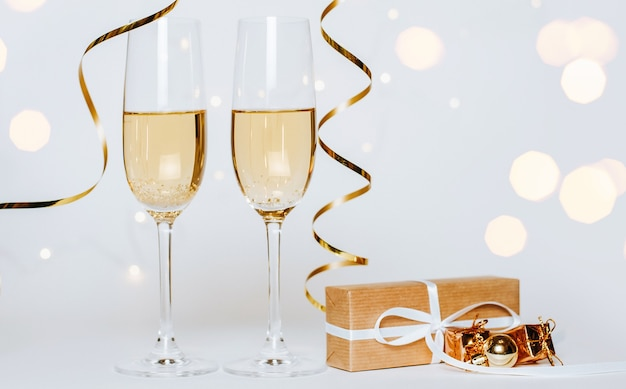 Duas taças de champanhe com luzes e fitas em um feriado branco