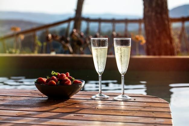 Duas taças de champanhe com um prato de morangos em um terraço ao lado da piscina