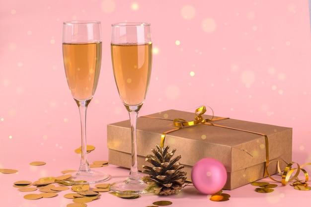 Duas taças de champanhe com um presente em um fundo rosa claro com bokeh dourado