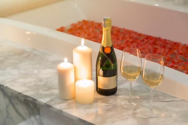 Duas taças de champanhe com vela perto de jacuzzi