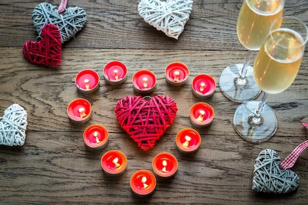 Duas taças de champanhe com velas acesas e corações de cana