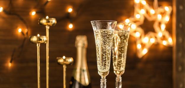 Duas taças de champanhe contra as luzes do feriado. símbolo da celebração do ano novo ou do natal. fundo de celebração de ano novo com champanhe dourado