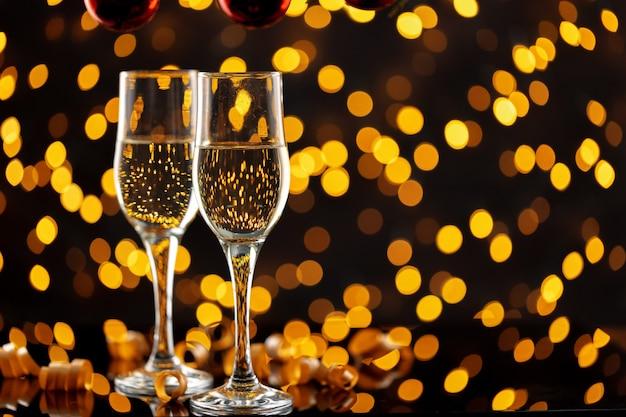 Duas taças de champanhe contra luzes brilhantes de bokeh