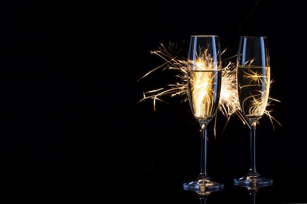 Duas taças de champanhe de vidro em luzes de bengala