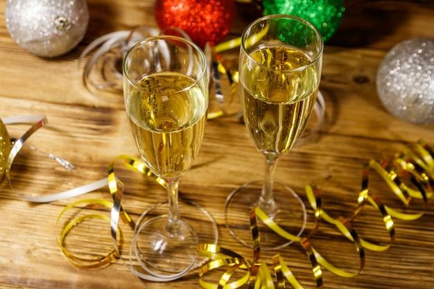 Duas taças de champanhe e decorações festivas de natal na mesa de madeira. celebração de natal e ano novo