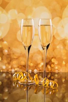 Duas taças de champanhe e fita com bokeh de luz dourada no fundo. jantar romântico. conceito de férias de inverno.