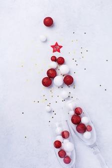 Duas taças de champanhe e garrafa de champanhe de natal com granulado em forma de árvore de natal feita de bolas de brinquedos vermelhas e brancas decoradas confetes dourados em branco.