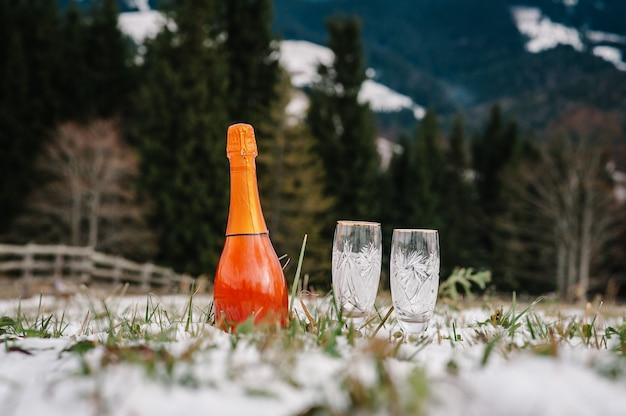 Duas taças de champanhe e uma garrafa de vinho espumante na neve na montanha.