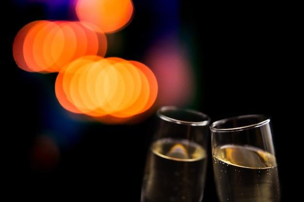 Duas taças de champanhe em fundo preto com luzes desfocadas. conceito festivo para celebração.