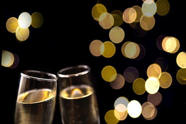Duas taças de champanhe em fundo preto com luzes desfocadas conceito festivo
