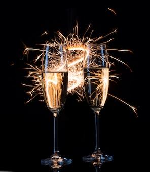 Duas taças de champanhe em traços ondulados de luzes de bengala