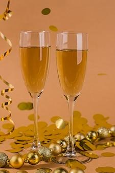 Duas taças de champanhe em um fundo bege com bokeh dourado e serpentina