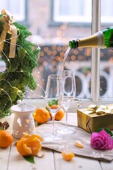 Duas taças de champanhe, frutas em cima da mesa perto da janela