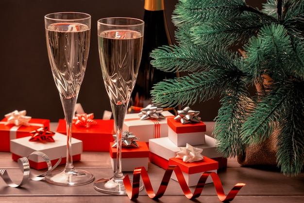 Duas taças de champanhe, muitas caixas de presente com laços e fitas decorativas.