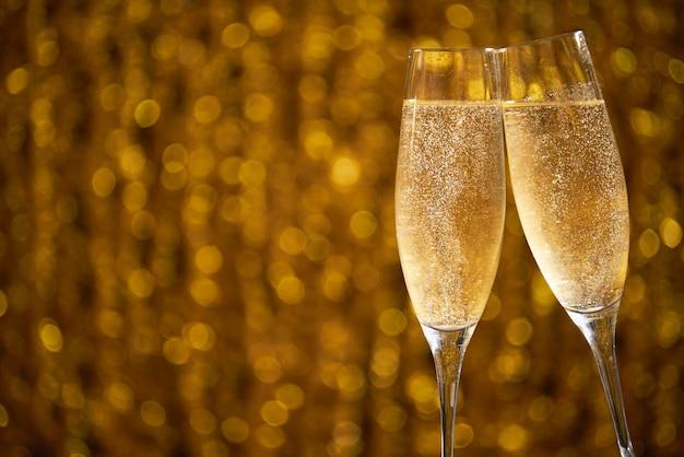 Duas taças de champanhe nos efeitos brilhantes bokeh