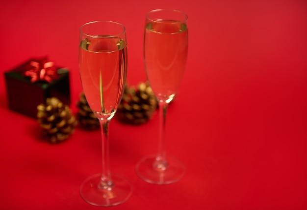 Duas taças de champanhe ou taças com espumante no fundo vermelho com pinhas ornamentadas com tintas douradas e um luxuoso presente de natal em papel de embrulho verde brilhante com laço vermelho glitter