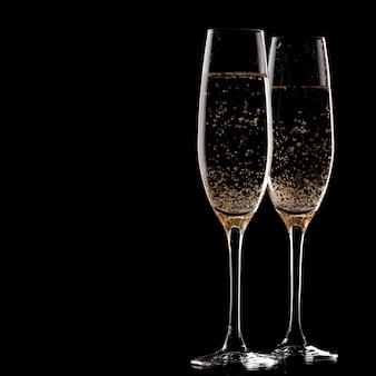 Duas taças de champanhe sobre fundo preto