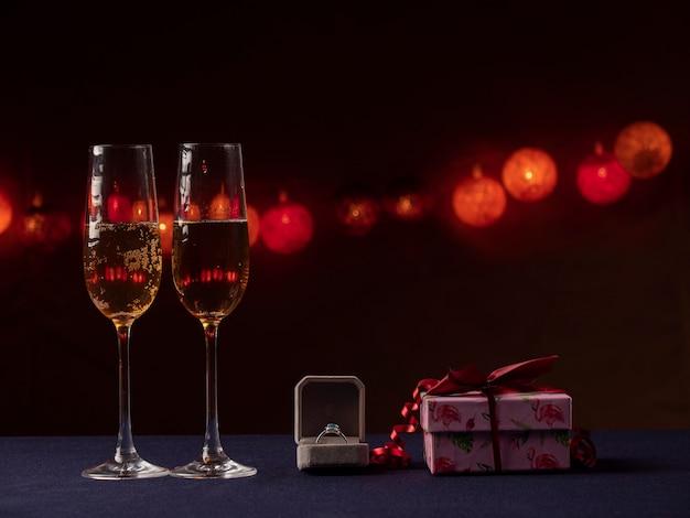 Duas taças de champanhe, uma caixa branca com um anel e um presente rosa ao lado de um fundo preto com luz