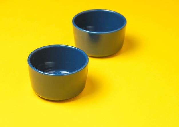 Duas taças de esmalte azul sobre fundo amarelo. vista do topo