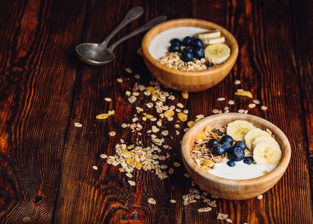 Duas taças de granola com banana, mirtilo e iogurte grego no café da manhã. muesli espalhado na mesa de madeira. copie o espaço à esquerda.