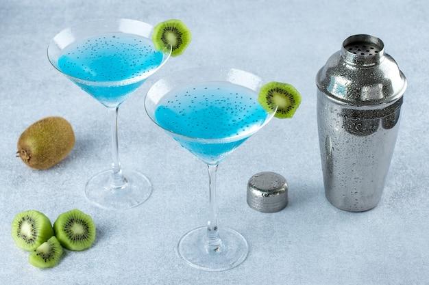 Duas taças de martini com kiwi e coqueteleira em um fundo cinza