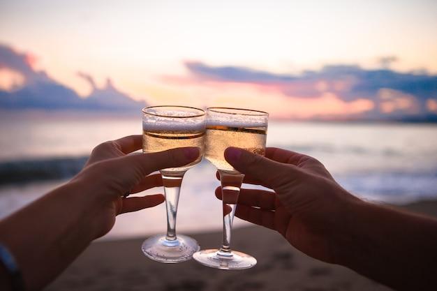 Duas taças de vinho branco na praia ao pôr do sol