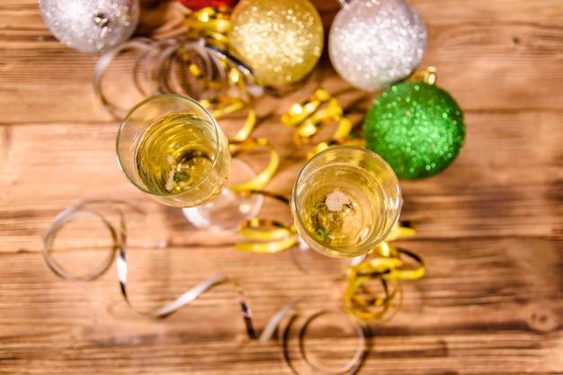 Duas taças de vinho com champanhe e diferentes decorações de natal na mesa de madeira rústica. vista do topo