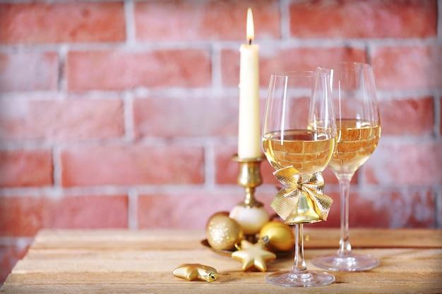 Duas taças de vinho com velas e brinquedos de natal no fundo da parede