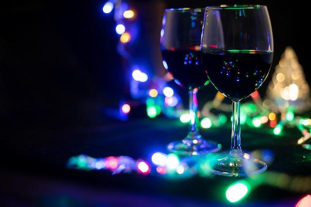 Duas taças de vinho em uma guirlanda brilhante com uma árvore de natal de brinquedo
