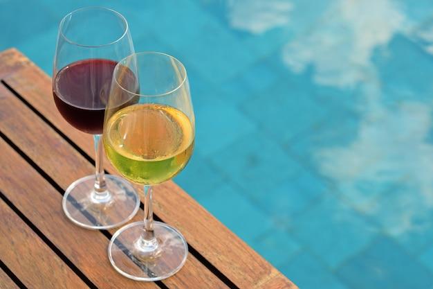 Duas taças de vinho na mesa de madeira ao lado da piscina no verão