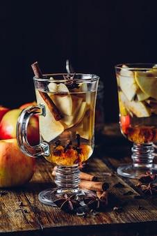 Duas taças de vinho quente de natal com maçã cortada
